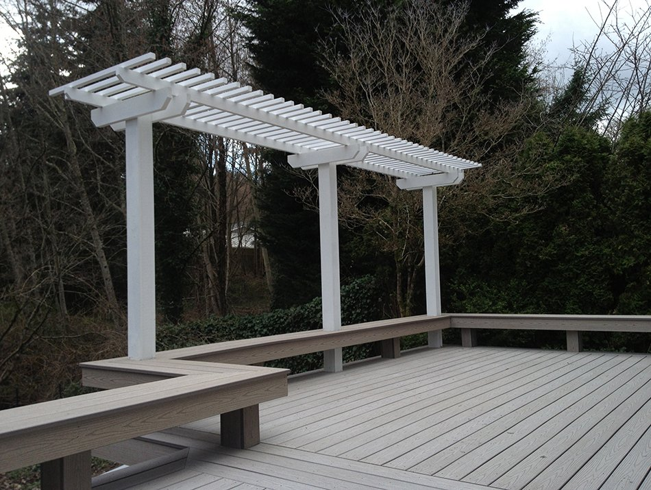 Composite deck with a bench and a pergola by Master Decks, LLC